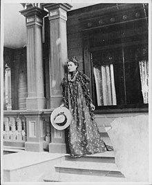 Likelike's daughter, standing on a porch in a long dress and holding a hat