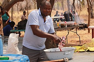 Botswana cuisine - Image: Kalanga man tenderising goat meat with a knife 2