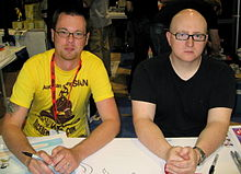 Two young men, Mike Krahulik and Jerry Holkins, sitting at a booth at a convention.