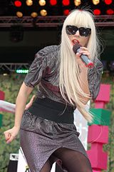 Lady Gaga with long blond hair, wearing a grey dress, a black belt and black sunglasses, singing into a microphone on an outdoor stage