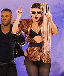 A blond woman wearing black sunglass and her hair in a side ponytail. She wears a black and gold printed shirt through which her bustier is seen. The woman wears black stockings and has both of her hands raised a little upwards. She is flanked on her right by man, who strikes a similar pose, wearing black vest and pants. They are standing in front of a light blue backdrop.