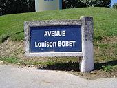 Photographie d'un panneau de rue avec des écritures blanches sur fond bleu.