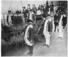 Виден большой колокол, привязанный к телеге.  Солдаты в форме времен войны за независимость стоят рядом.