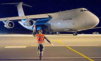 9th Airlift Squadron - 9th Airlift Squadron C-5B 86-0020 is marshalled out of its parking spot for a four-day mission March 8, 2012.  This was the last active-duty C-5B mission flown at Dover AFB.
