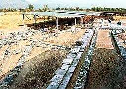 Vestiges au sol avec une colonne en arrière-plan et une toiture moderne de protection.