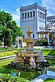 München, Brunnen im Garten des Lenbachhauss. Im Hintergrund das Propyläen am Königsplatz (8889866459).jpg