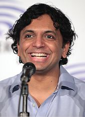 A 45-year-old man is shown in a head shot. He is broadly smiling and is in front of a microphone.