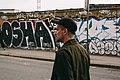 Man walks in front of graffiti wall (Unsplash).jpg