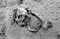 Massagraf van ontvoerde Chinezen op het terrein van de vernielde fabriek van de rubberonderneming Badek, district Wates. Een aan de rechterzijde gescheurde schedel.jpg