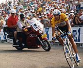 A man on a bicycle wearing a helmet with a visor and a yellow top with black shorts. In the background there is a red motorcycle with two men on it.