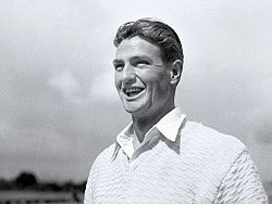 Young man with dark hair parted in the middle, grinning and wearing a white open collar shirt and a white jumper