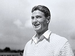 Young man with dark hair parted in the middle, is grinning and wears a white open collar shirt and a white jumper.