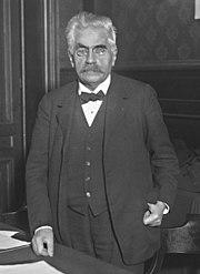 Zwart-witfoto van een man die in een kantoor staat: hij heeft grijswit haar, dikke zwarte wenkbrauwen, een grijze snor, bril, een vlinderdas en een driedelig pak