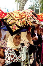 Women carrying platters of food to a ceremony
