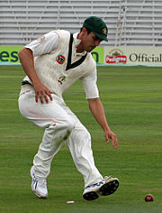 Mitchell Johnson is bending down to pick up a red cricket ball with his left hand. He is on the run.