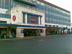 "Station entrance in the form of a white stone-clad box sitting on two substantial and wide stone blocks. The front facade of the box contains a large London Underground logo (red ring with blue horizontal bar across the centre containing the word ""UNDERGROUND"") in the centre. Set back behind the entrance and to both sides a four-storey office block with blue cladding rises up."