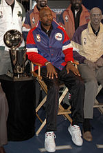 A black man wearing a blue and red jacket sits on a wooden chair. Several others and a trophy sit next to him