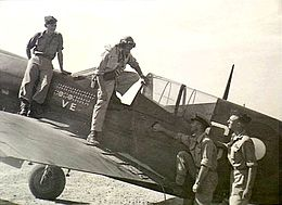 "Pilot with goggles emerging from cockpit of single-engined monoplane which has the letters ""VE"" prominently displayed on its fuselage, in company with three other men"