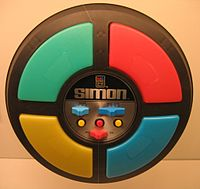 The game is a a circular disc divided intjln, o four quarter circle buttons each with a different color. In the center are the game mode controls