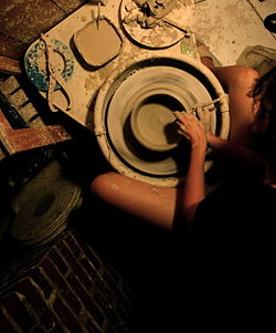 A potter in Memphis, Tennessee shapes a piece of pottery on a variable-speed, electric-powered potter's wheel.