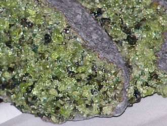 Pyroxene - Mantle-peridotite xenolith from San Carlos Indian Reservation, Gila Co., Arizona, USA. The xenolith is dominated by green peridot olivine, together with black orthopyroxene and spinel crystals, and rare grass-green diopside grains. The fine-grained gray rock in this image is the host basalt.(unknown scale)