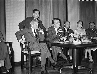 George Stevens Jr. - George Stevens Jr., associate producer of The Diary of Anne Frank, speaks at a press conference in Amsterdam in July 1958. Music director Alfred Newman is seated at left.