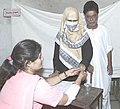 Poll personnel administering indelible ink to a woman voter in old Lucknow, Uttar Pradesh during the third phase of General Election-2004 on May 5, 2004.jpg