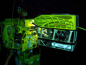 Remotely operated underwater vehicle - ROV at work in an underwater oil and gas field. The ROV is operating a subsea torque tool (wrench) on a valve on the subsea structure.
