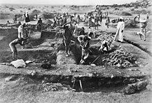 A black and white photograph of an archaeological excavation site