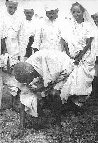 Salt March - Gandhi picking up grains of salt at the end of his march, Behind him is his second son Manilal Gandhi and Mithuben Petit.
