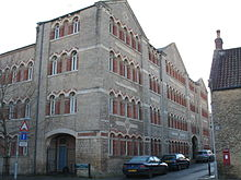 Corner of four storey building with multiple matching arched windows