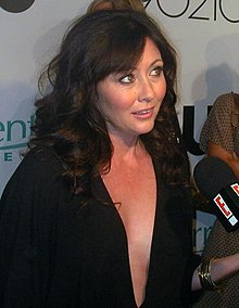 A woman with shoulder-length black hair wearing a black dress with a plunging neckline speaks to a reporter.