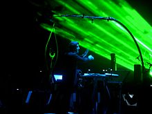 Dirk Brossé conducting as green lasers shine in the background