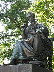 Photo en couleur de la statue en bronze d'un homme assis vêtu à la mode romaine.