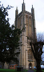 Decorated and buttressed yellow stone tower.