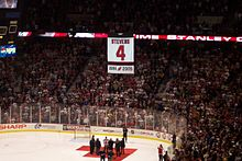A large white banner with the number 4 is suspended in air above an ice hockey rink, as the crowd cheers.