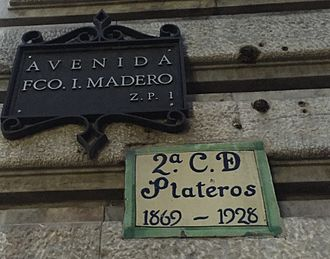 Madero Street - Modern street sign and plaque with the former name of the section, Calle de Plateros.