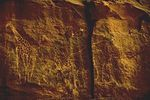 A picture of a very faint drawing of an elephant and a giraffe on a cave wall.