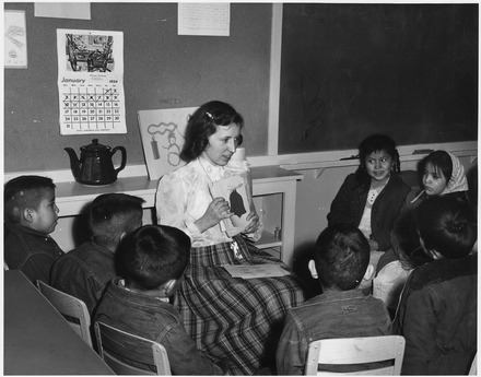 Teacher with picture cards giving English instruction to Navajo day school students (Teacher with picture cards giving English instruction to Navajo day school students.) - NARA - 295158.tif