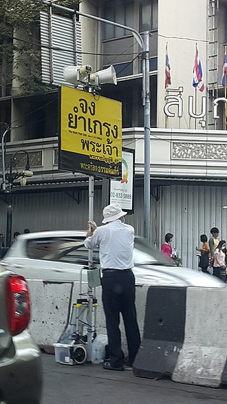 Bible translations - A man holding the sign persuading people to read Bible in Thai at Sala Daeng BTS Station, Bangkok