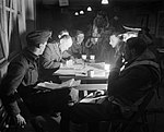 The crew of a Short Stirling bomber of No. 622 Squadron RAF being debriefed by the intelligence officer at Mildenhall, Suffolk, after returning from the major raid on Berlin of 22-23 November 1943. CH11641.jpg