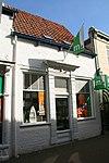 foto van Eenvoudig pand met geverfde gevel waarin kielbogen van de oorspronkelijke architectuur zichtbaar zijn