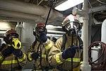 U.S. Navy Gas Turbine Systems Technician (Mechanical) 3rd Class Kathren Shost, right, Damage Controlman 3rd Class Brandon Williams, center, and Damage Controlman Fireman Jonathan Church participate in a general 140103-N-UD469-417.jpg