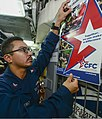 U.S. Navy Logistics Specialist 2nd Class Dionicio Moreno hangs a Combined Federal Campaign poster Oct. 3, 2013, aboard the guided missile cruiser USS Monterey (CG 61) in the Persian Gulf 131003-N-QL471-036.jpg