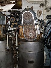 The vapour-compression distiller installed in the submarine's engine room. A cylindrical drum water vessel carries the compressor and its electric motor with belt drive above it.