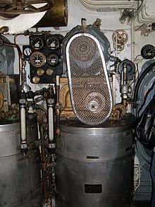 The vapour-compression destiller installed in the submarine's engine room. A cylindrical drum water vessel carries the compressor and its electric motor with belt drive above it.