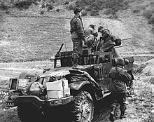 Several soldiers working around a machine gun mounted on a half-track