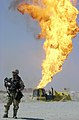 US Navy 030402-N-5362A-010 A U.S. Army soldier stands guard duty near a burning oil well in the Rumaylah Oil Fields.jpg