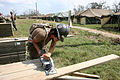 US Navy 050912-N-6027E-002 U.S. Navy Builder Constructionman Lisseth Briceno, assigned to Naval Mobile Construction Battalion Four Zero (NMCB-40), cuts wood for a National Guard tent city.jpg