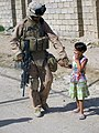 US Navy 070615-M-XXXXX-001 Hospital Corpsman 3rd Class Oscar Martinez, assigned to 3-7 Bn. Weapons Co. 1st Marine Division, is greeted by an Iraqi girl.jpg